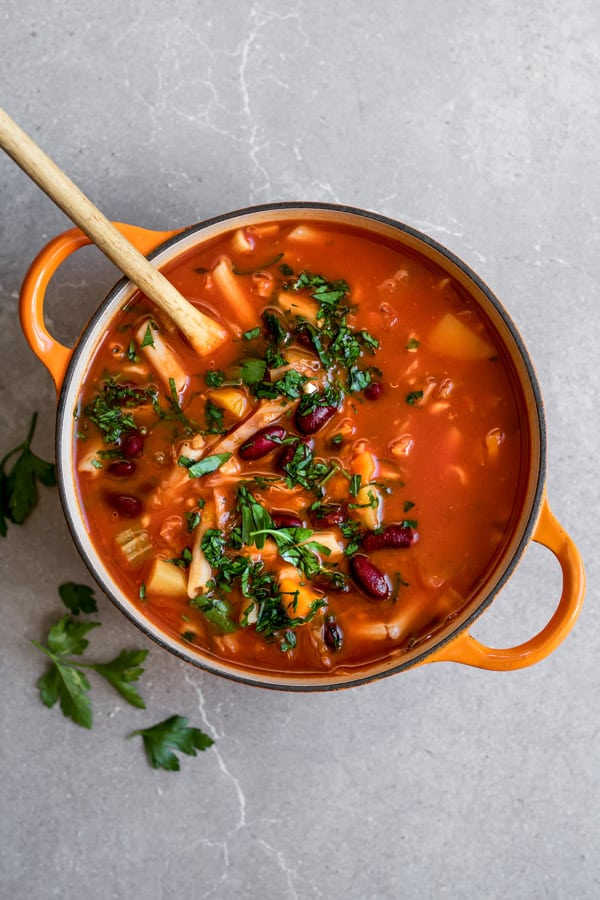 Cozy up with a bowl of this one pot vegan minestrone soup! It takes less than 30 minutes to make and is loaded with hearty good for you ingredients!