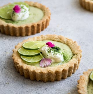a mini key lime pie topped with sliced limes and whipped coconut cream