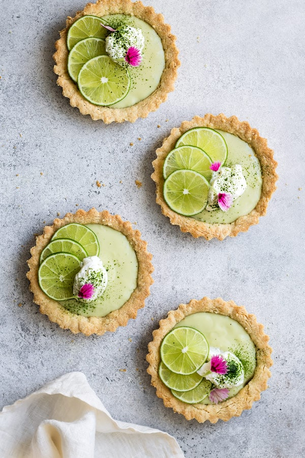 four mini vegan key lime pies with whipped coconut cream limes and flower petals on top