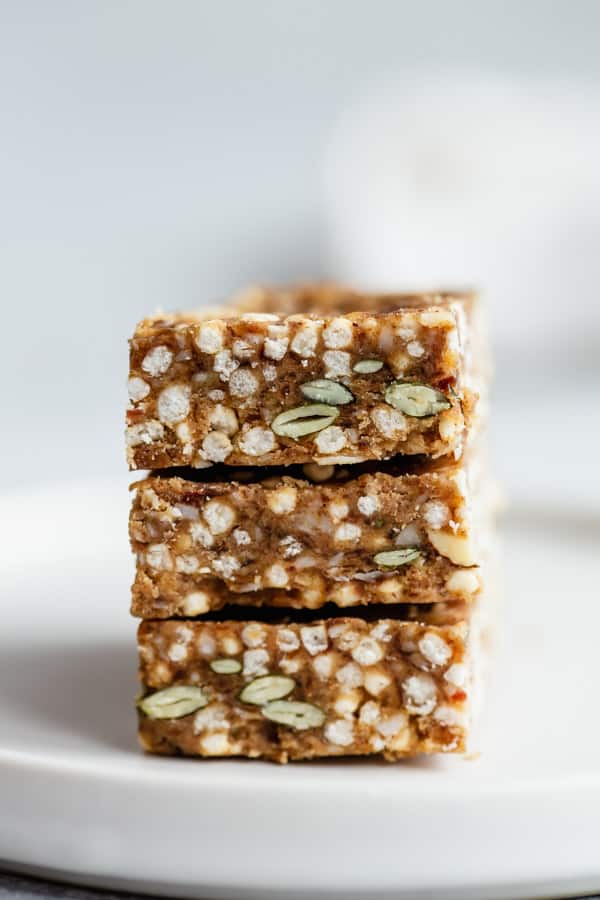 three puffed quinoa bars stacked on a plate with a napkin in the background