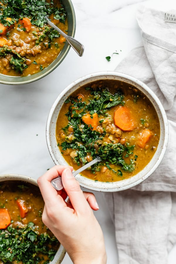 a hand scooping a spoon in a bowl of slow cooker lentil soup