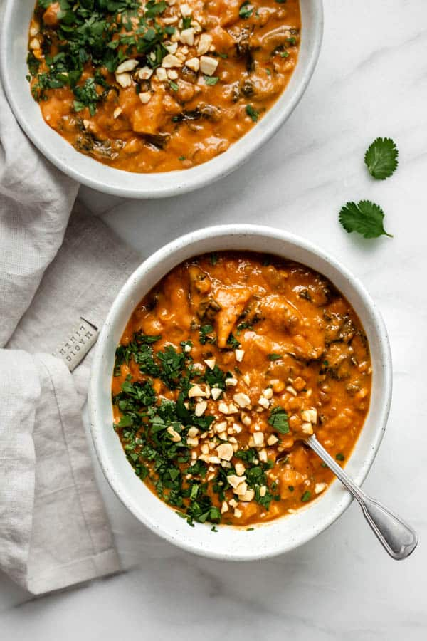 two bowls of West African peanut stew on a marble board with some cilantro on the side