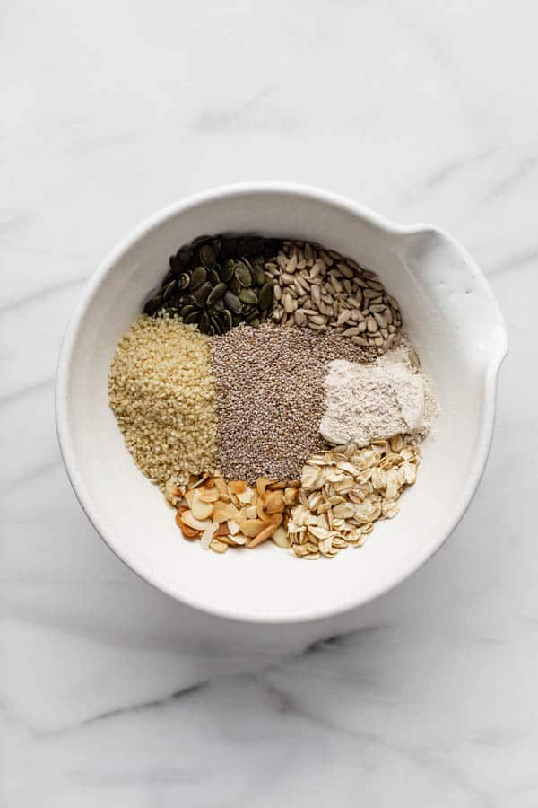 a mixing bowl with piles of seeds, nuts and oats in it