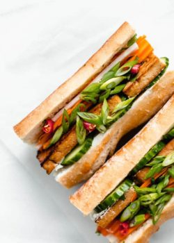 a plate with a tofu banh mi sandwich filled with pickled vegetables