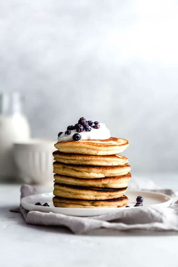 almond flour pancakes topped with blueberries, yogurt and maple syrup