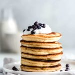 almond flour pancakes on a white plate topped with blueberries