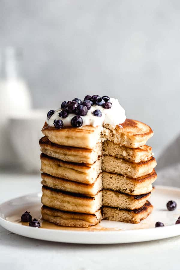 a stack of almond flour pancakes with a bite taken out of them