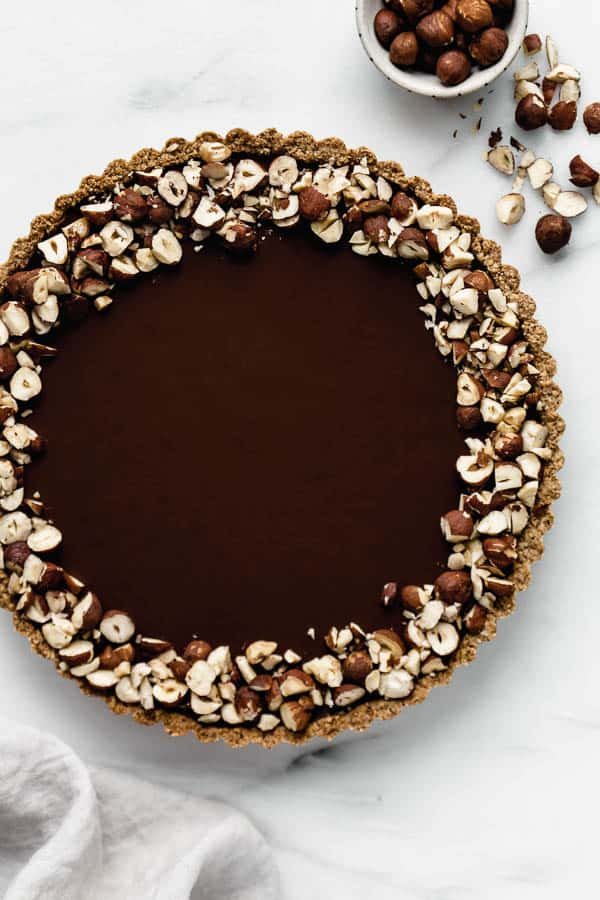 a chocolate hazelnut tart topped with crushed hazelnuts
