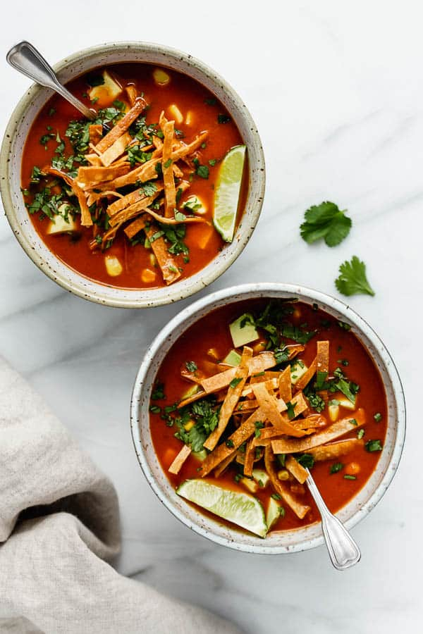 a tortilla soup topped with tortilla strips and fresh cilantro