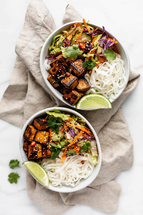 two bowls filled with Vietnamese salad, rice noodles and lemongrass tofu