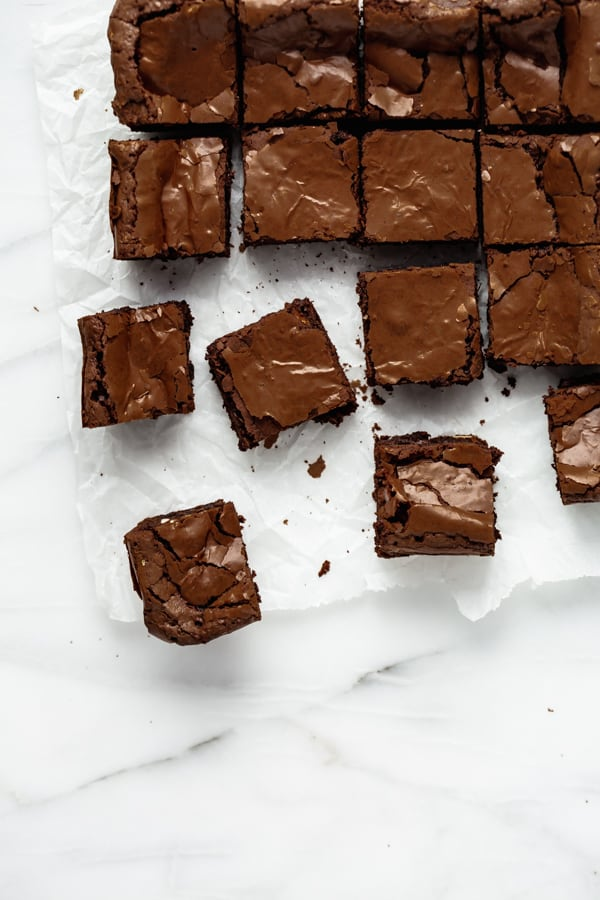 cut up chocolate brownies on a marble pastry board
