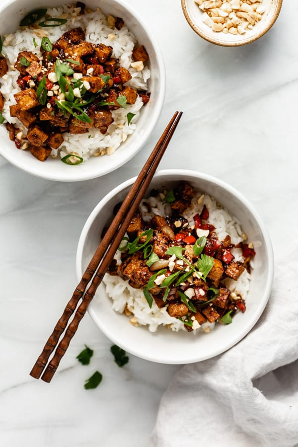 two bowls of kung pao tofu with chopsticks