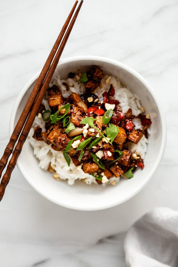 A white bowl with kung pao tofu and rice in it