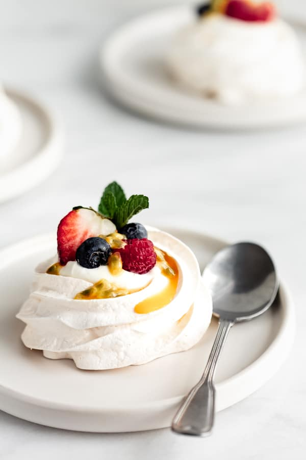 mini pavlovas with coconut whipped cream on a plate with a spoon