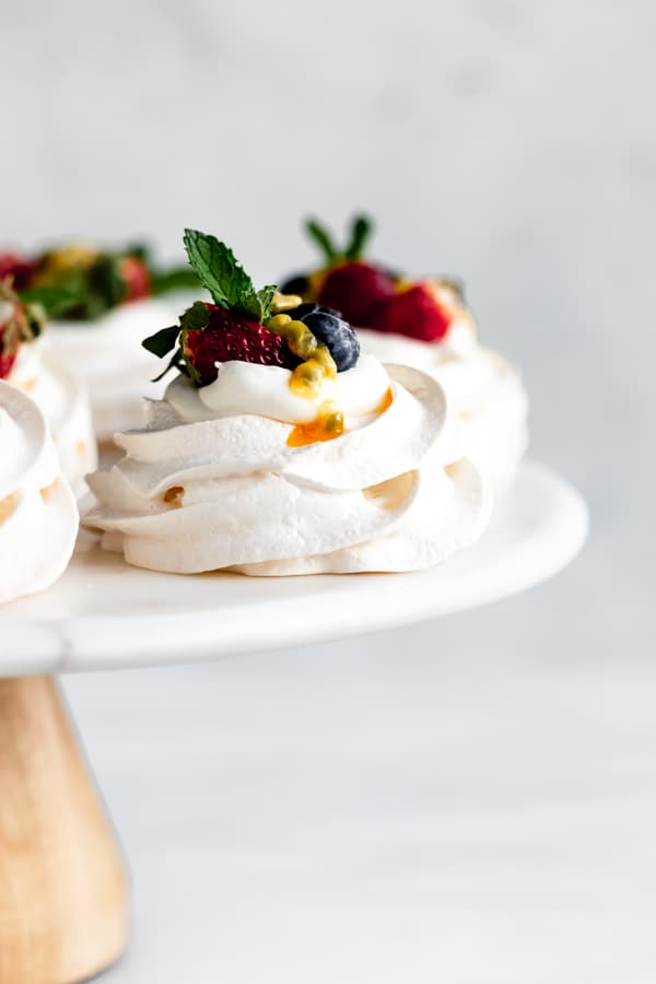 mini pavlovas with coconut whipped cream on a cake stand