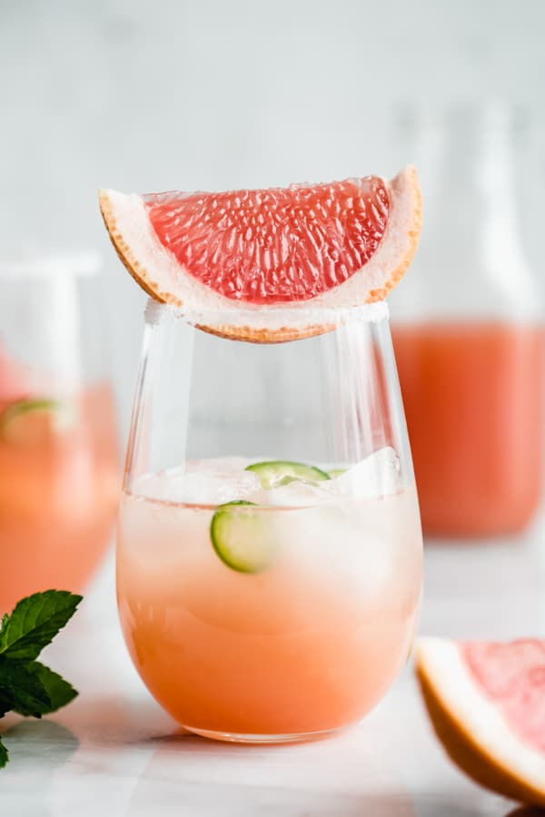 a grapefruit margarita in a glass with a wedge of grapefruit on top
