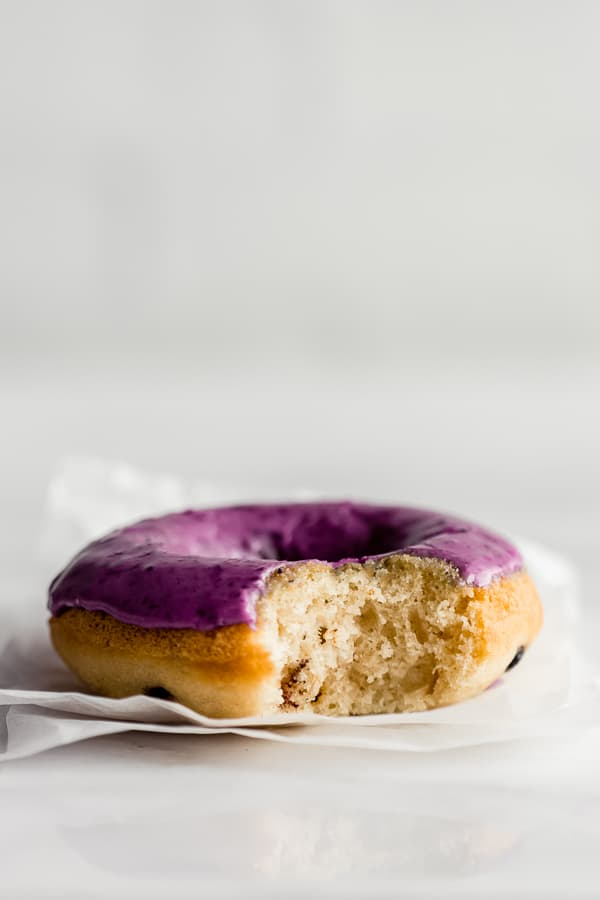 A close up of a blueberry donut with blueberry glaze with a bite taken out of it