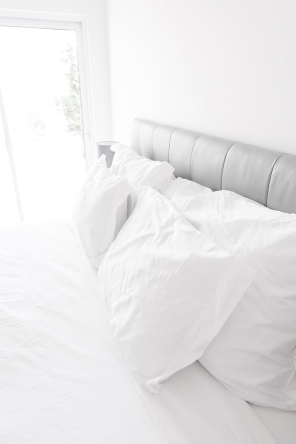 A white bed with white pillows