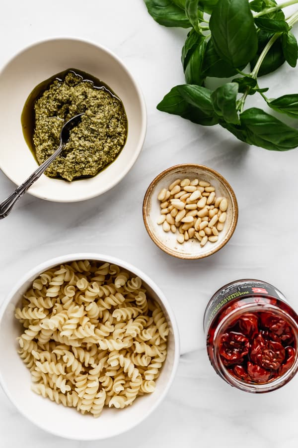 pesto, basil, pine nuts, sun-dried tomatoes and pasta on a marble board
