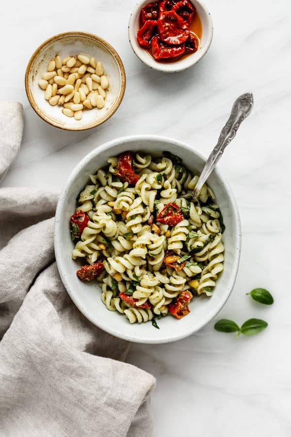 a bowl of pesto pasta salad with a napkin and some pine nuts on the side