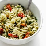 a close up image of a bowl of pesto pasta salad