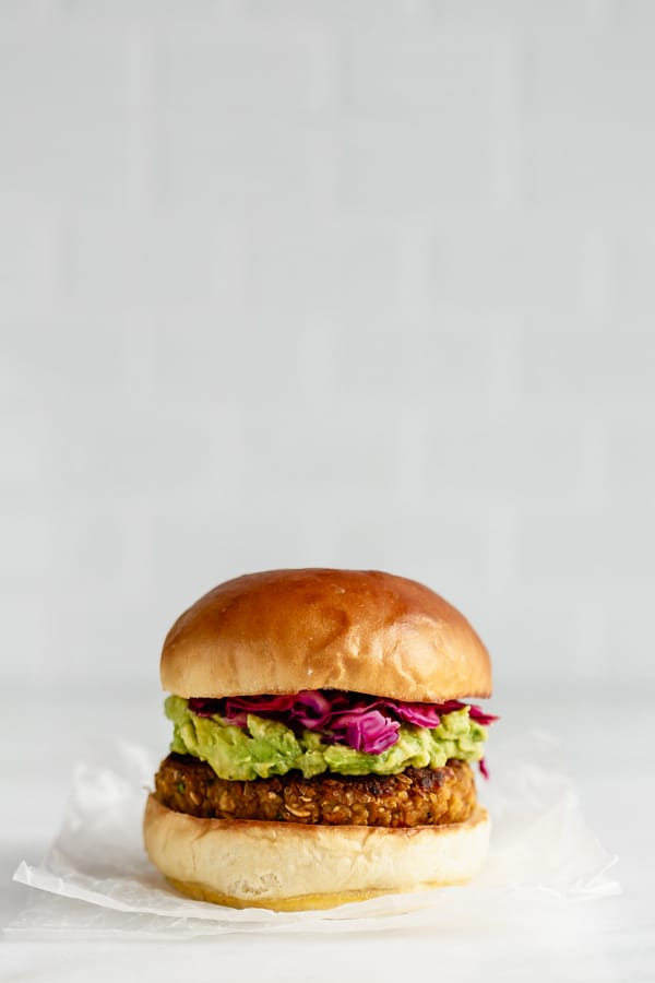 a chickpea veggie burger with avocado, cabbage and a bun