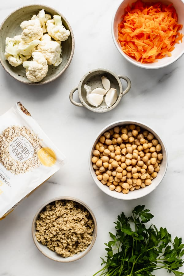 carrots, cauliflower, garlic, oats, quinoa, chickpeas and parsley on a marble board