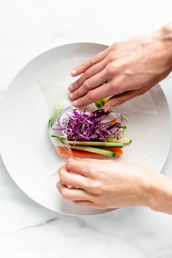 hands folding vegetables in a rice paper wrapper