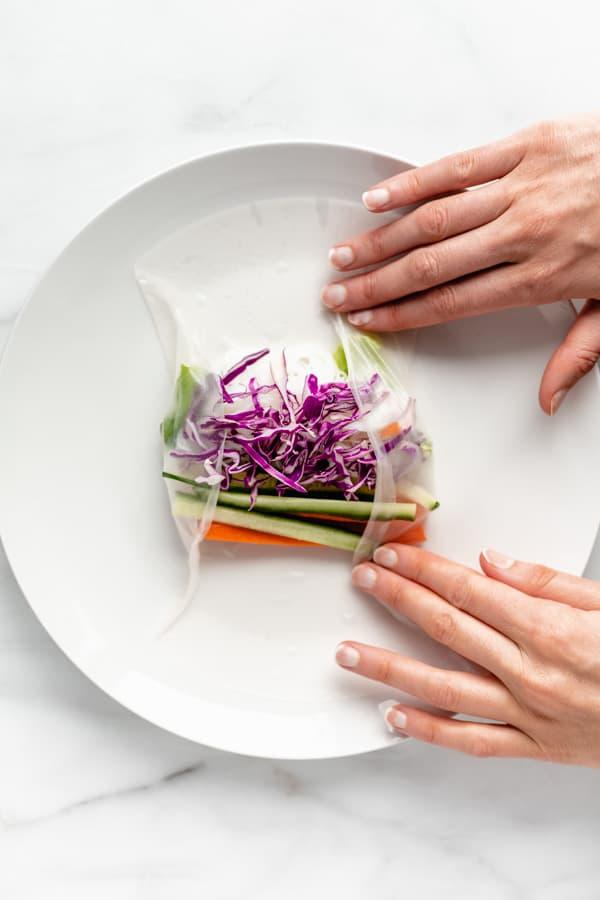 two hands making a vietnamese summer roll
