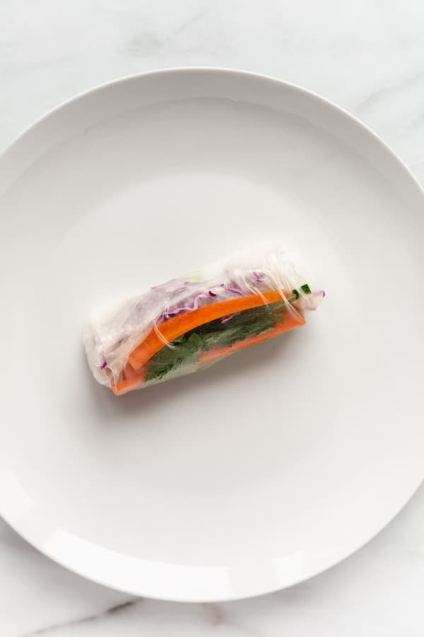 A rolled up Vietnamese fresh spring roll on a white plate