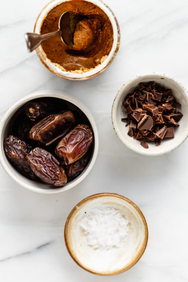 dates, almond butter, chocolate and sea salt on a marble board