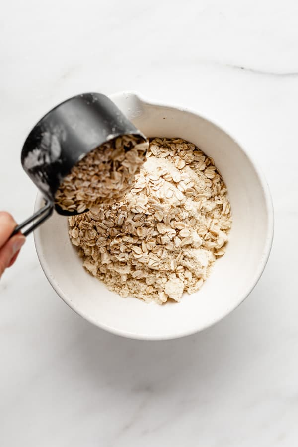 pouring oats into a mixing bowl