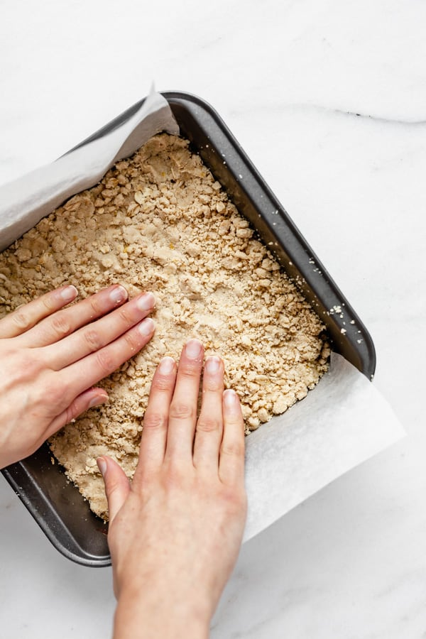 two hands pressing dough into an 8x8 inch pan