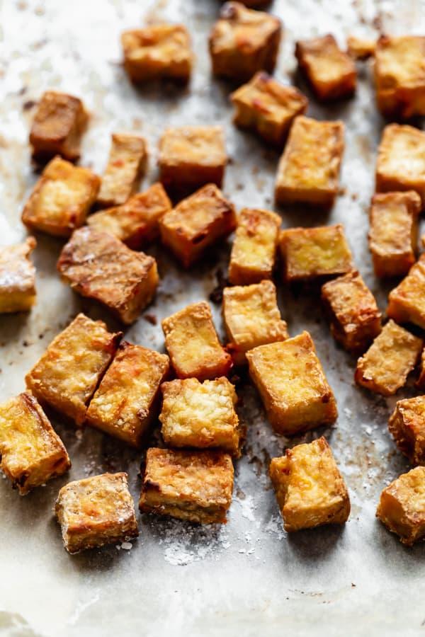 crispy tofu cut in cubes on a baking sheet