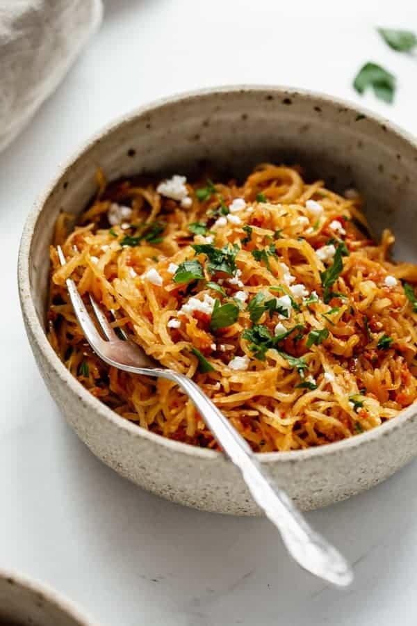 a close up of sun dried tomato spaghetti squash in a ceramic bowl