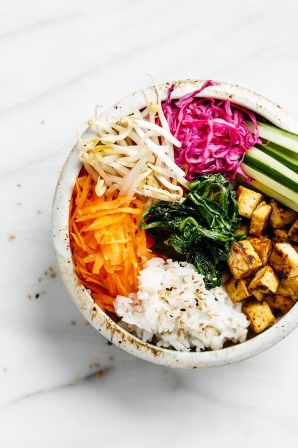 a bowl with carrots, rice, tofu and vegetables