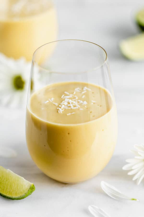a glass of vegan mango lassi on a marble board with limes and flowers