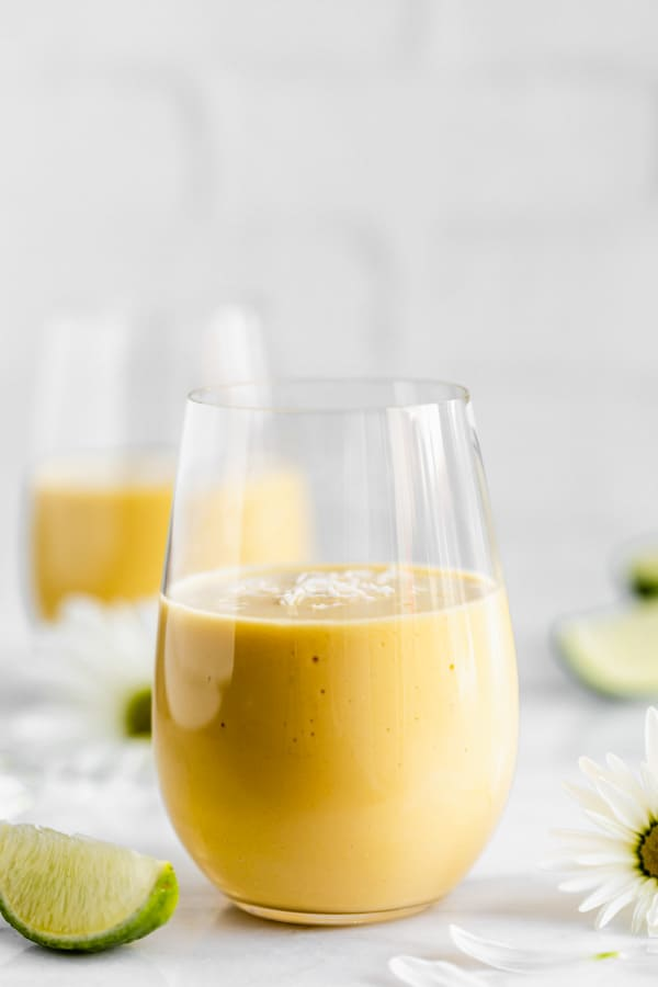 a glass of vegan mango lassi with shredded coconut on top