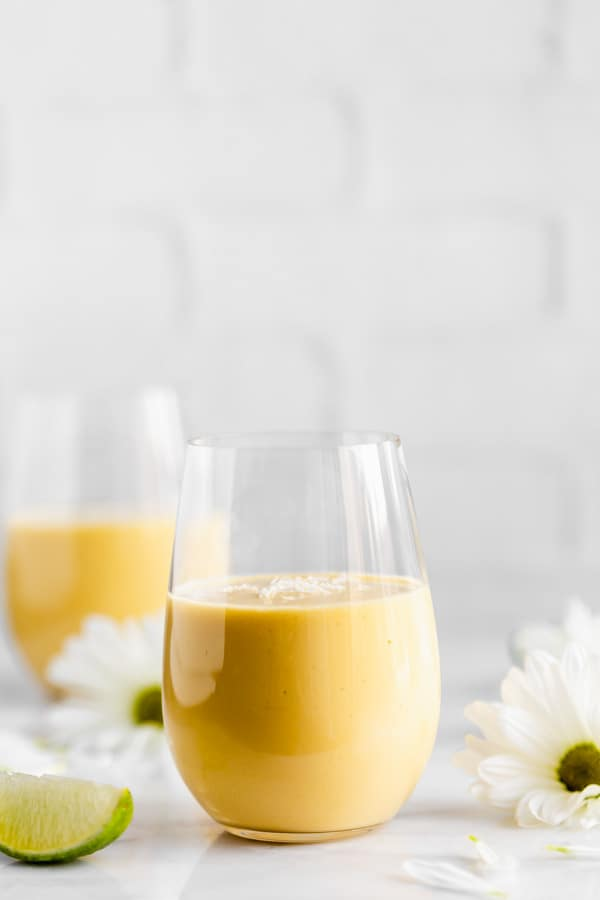 a glass of vegan mango lassi with flowers in the background