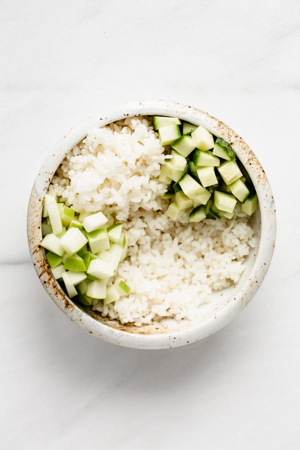 bowl with rice cucumber and cut up green apple
