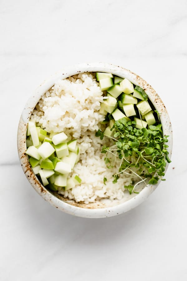 bowl with rice, cucumber, apple, and green sprouts