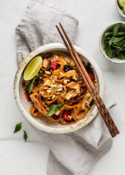 a bowl of drunken noodles on a napkin with chopsticks