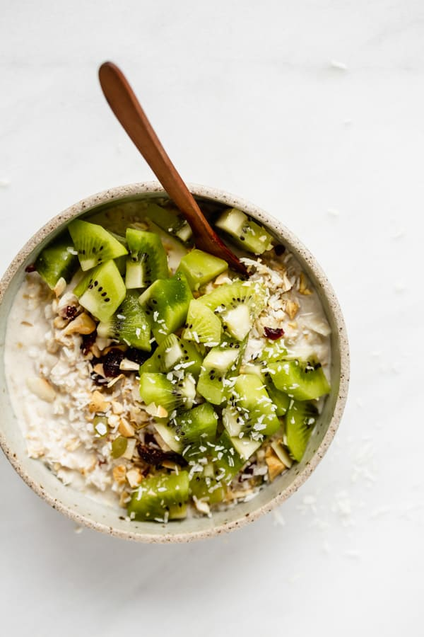 a bowl of bircher muesli with a wood spoon in it