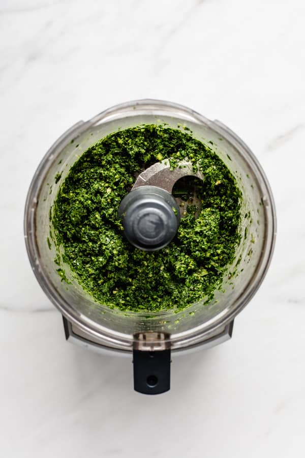 a food processor with kale pesto in it