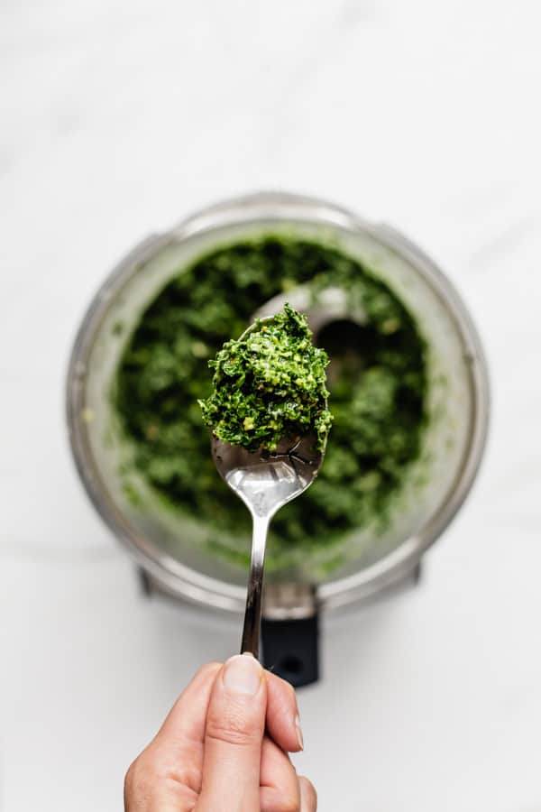 a hand holding a spoon of kale pesto