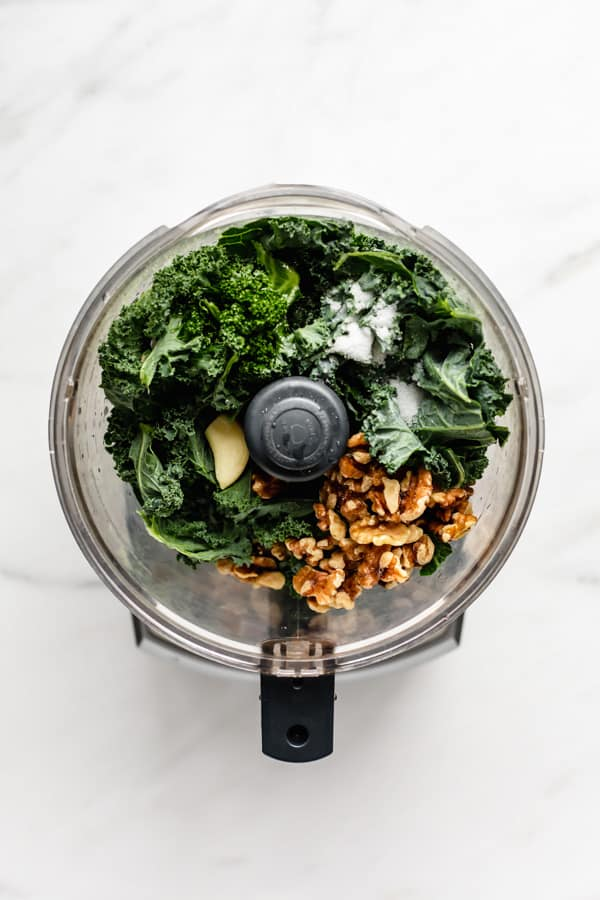 a food processor with kale, walnuts, garlic and salt in it