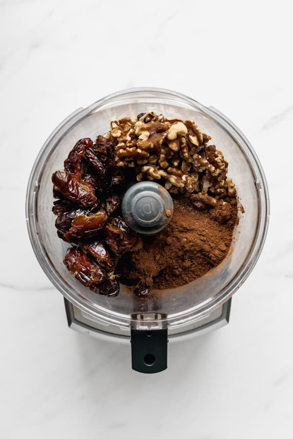 a food processor with dates walnuts and cocoa