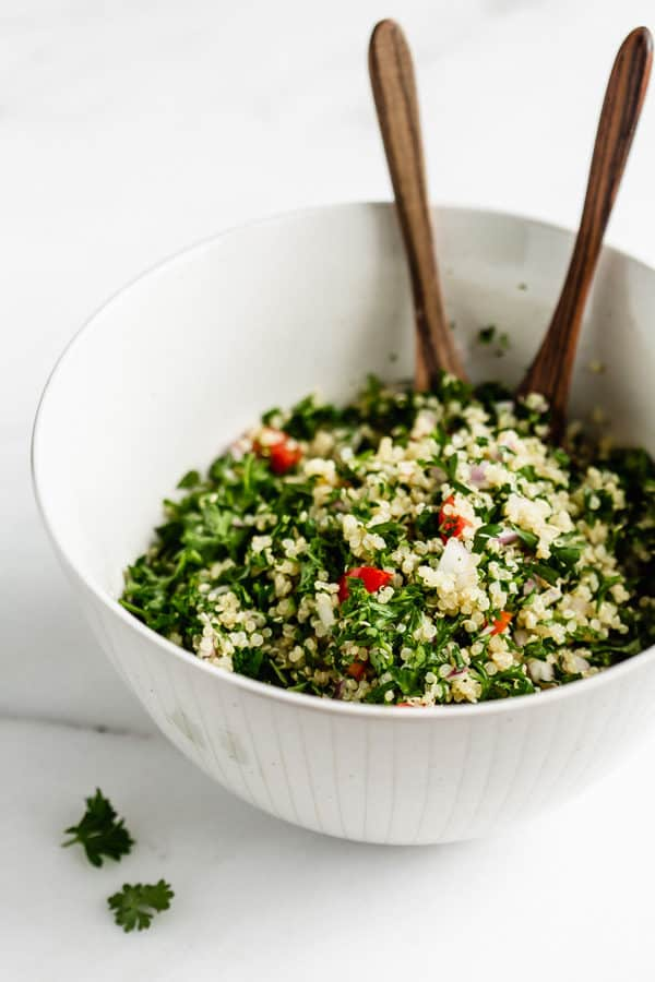 quinoa tabbouleh in a serving bowl with serving spoons