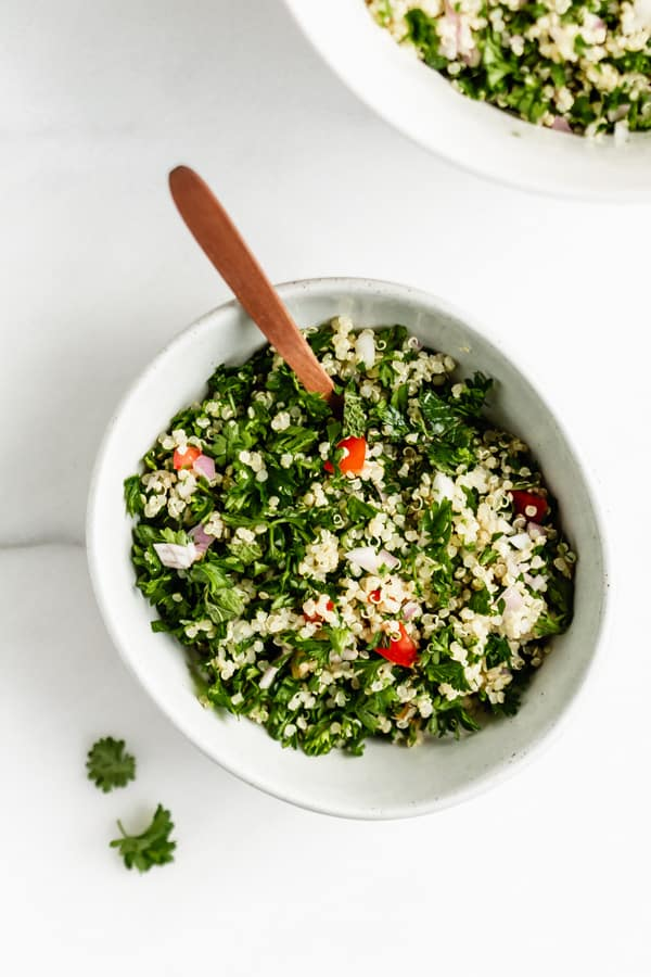 a bowl of quinoa tabbouleh with a spoon in it