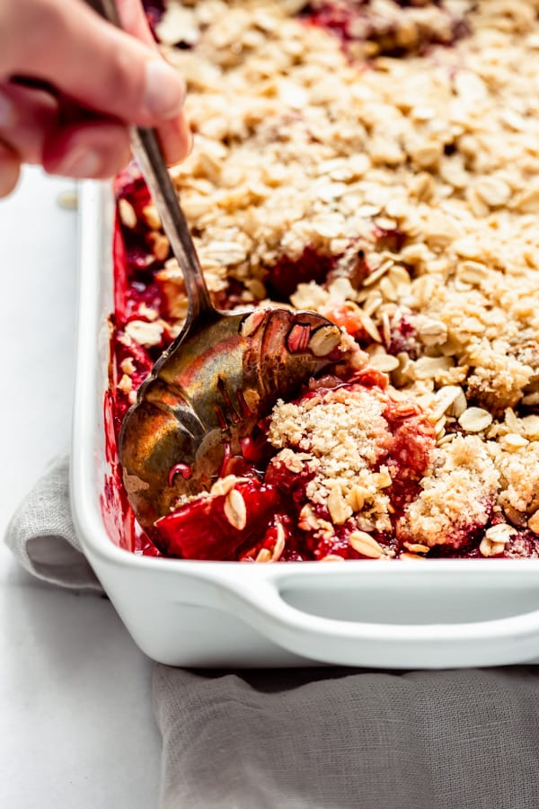 a serving spoon scooping a piece of strawberry rhubarb crisp